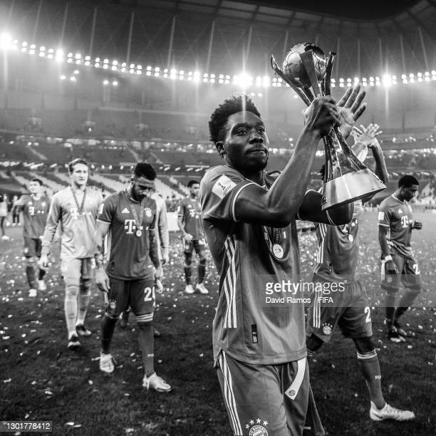 Alphonso Davies of FC Bayern Muenchen celebrates with the trophy after winning the FIFA Club World Cup Qatar 2020 Final between FC Bayern Muenchen...