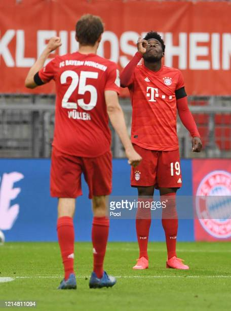 Alphonso Davies of FC Bayern Muenchen celebrates with Thomas Muller after scoring his team's fourth goal during the Bundesliga match between FC...