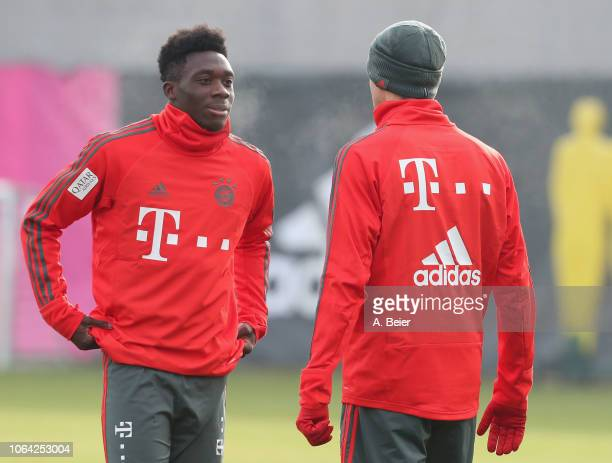 Alphonso Davies of FC Bayern Muenchen chats with Thomas Mueller during a training session at the club's Saebener Strasse training ground on November...