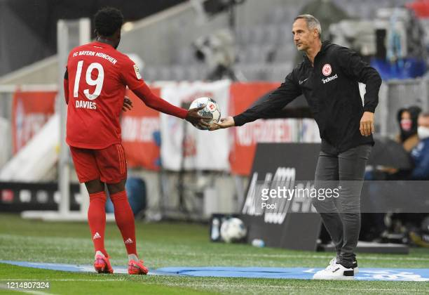 Alphonso Davies of FC Bayern Muenchen collects the ball from Adi Hutter Manager of Eintracht Frankfurt during the Bundesliga match between FC Bayern...