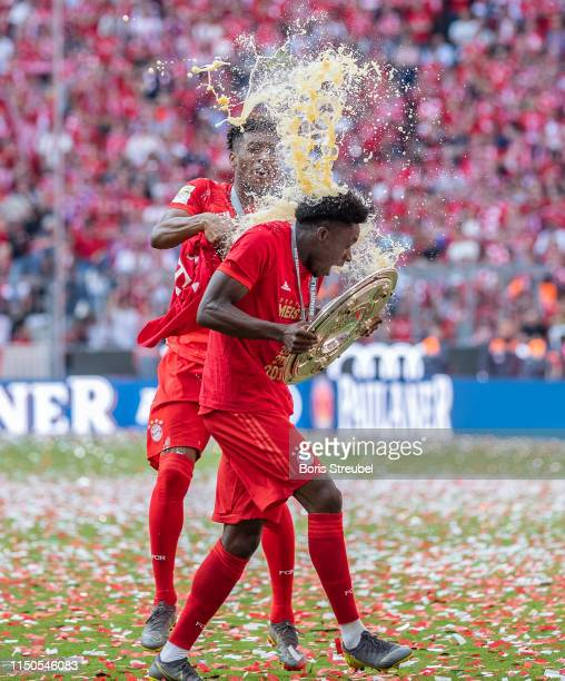 Alphonso Davies of FC Bayern Muenchen gets a beer shower from Kingsley Coman of FC Bayern Muenchen to celebrate the championship following the...