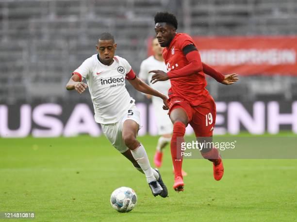 Alphonso Davies of FC Bayern Muenchen is challenged by Gelson Fernandes of Eintracht Frankfurt during the Bundesliga match between FC Bayern Muenchen...