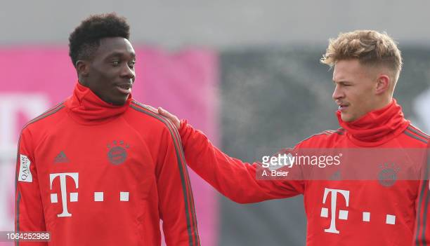 Alphonso Davies of FC Bayern Muenchen jokes with Joshua Kimmich during a training session at the club's Saebener Strasse training ground on November...
