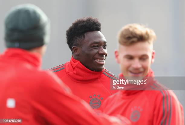 Alphonso Davies of FC Bayern Muenchen jokes with Joshua Kimmich and Thomas Mueller during a training session at the club's Saebener Strasse training...