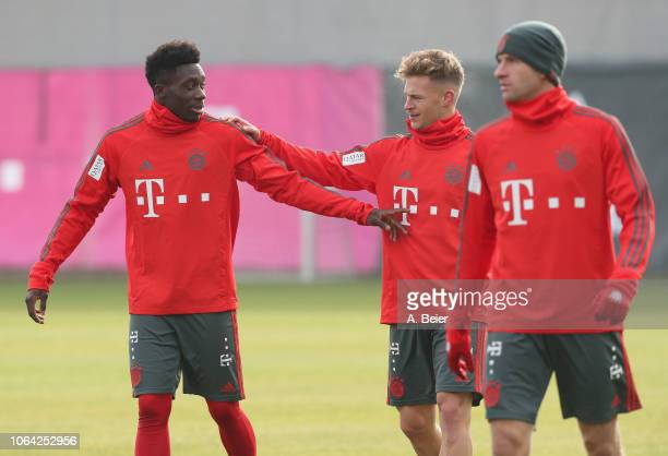 Alphonso Davies of FC Bayern Muenchen jokes with Joshua Kimmich next to Thomas Mueller during a training session at the club's Saebener Strasse...
