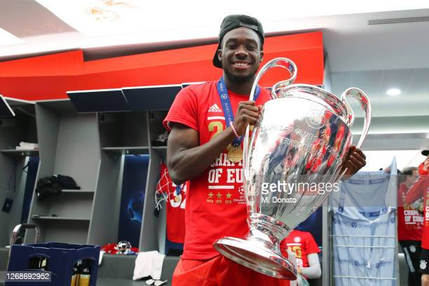 Alphonso Davies of FC Bayern Muenchen poses with the trophy in the dressing room following his team's victory in the UEFA Champions League Final...