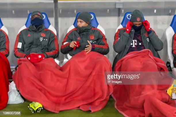 Alphonso Davies of FC Bayern Muenchen Serge Gnabry of FC Bayern Muenchen and Jerome Boateng of FC Bayern Muenchen on the bench during the Bundesliga...