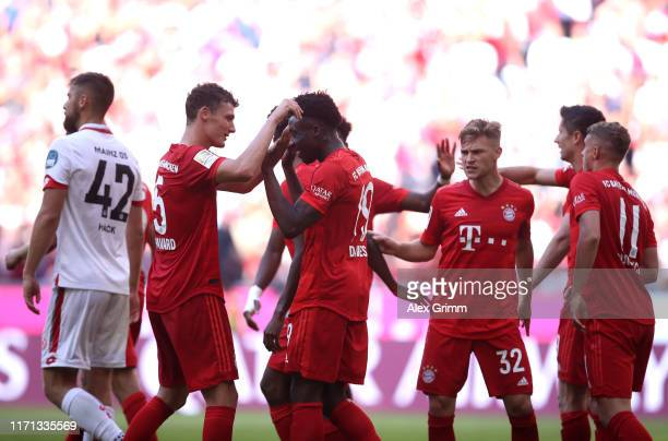 Alphonso Davies of FC Bayern Munich celebrates with team mate Benjamin Pavard after scoring his team's sixth goal during the Bundesliga match between...