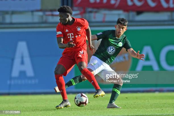 Alphonso Davies of Muenchen and Murat Saglam of Wolfsburg fight for the ball during the Third League Playoff First Leg match between VfL Wolfsburg II...