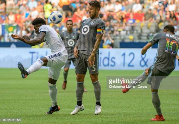 Alphonso Davies of the Vancouver Whitecaps and Francisco Calvo of Minnesota United duck from the ball kicked by Romario Ibarra of Minnesota United at...
