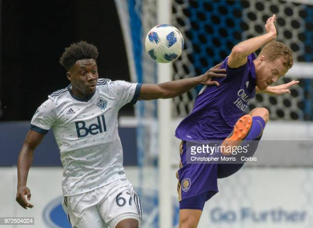 Alphonso Davies of the Vancouver Whitecaps and Oriol Rosell of Orlando City fight for the ball during a match between Orlando City SC and Vancouver...