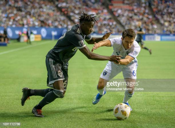 Alphonso Davies of the Vancouver Whitecaps and Shea Salinas of the San Jose Earthquakes fight for the ball at BC Place on September 1 2018 in...