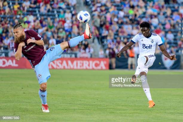 Alphonso Davies of Vancouver Whitecaps attempts a pass over Enzo Martinez of Colorado Rapids at Dick's Sporting Goods Park on June 1 2018 in Commerce...