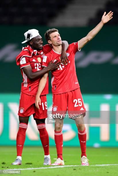 Alphonso Davies und Thomas Müller of Bayern Muenchen celebrate after winning the DFB Cup final match between Bayer 04 Leverkusen and FC Bayern...