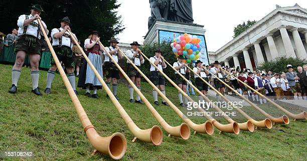 Alphorn musicians perform in front of the Bavaria monument during the Oktoberfest openair concert at the Theresienwiese in Munich southern Germany on...