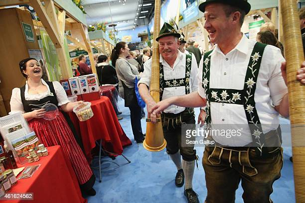 Alpine horn blowers from Bavaria walk among stands at the International Green Week agricultural trade fair on January 16 2015 in Berlin Germany The...