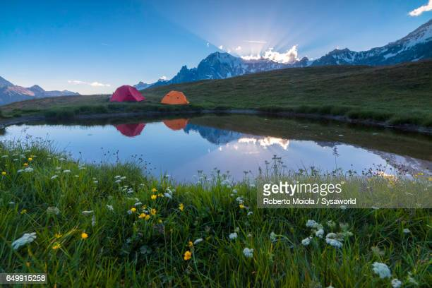 Alpine lake and camping tents Mont De La Saxe
