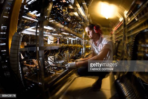 Alpine Mining cofounder and CEO Ludovic Thomas works at company's main cryptocurrency mining site jampacked with metal racks lined with hundreds upon...