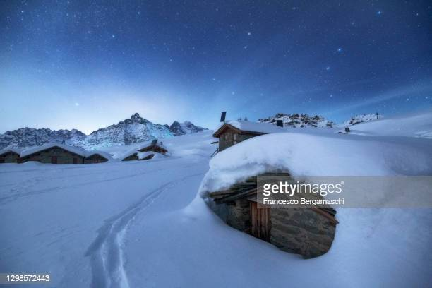 alpine pasture with traditional huts covered by heavy snow during a winter night. - italia stockfoto's en -beelden