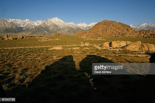 Alpine peaks of the Sierra Nevada Mountains which carry less snow than normal rise in the distance beyond the desertlike Alabama Hills where many...