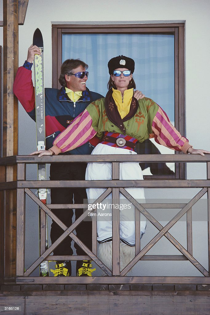 Alpine ski champion Max Rieger on the balcony of a villa in Gudari, in the Caucasus mountains,Georgia. With him is Meg O'Neil dressed in ski suit designed by Bogner and wearing with it an Aeroflot flight cap and mirror sunglasses.