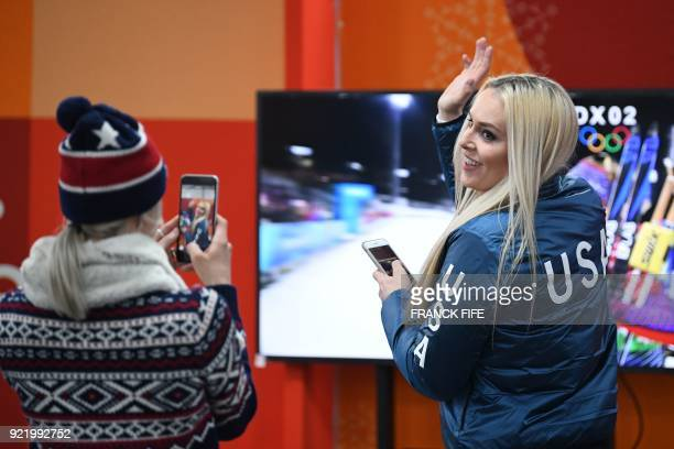Alpine skiing women's downhill bronze medallist USA's Lindsey Vonn reacts as she watches a live broadcast of the US team winning the cross country...