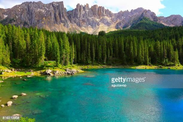 Alpine turkos Carezza lake (Lago di Carezza eller Karersee), idylliskt landskap nära majestätiska Latemar massivet Alperna valley, dramatiska italienska South Tirol Dolomiterna snötäckta bergskedjan panorama, Italien