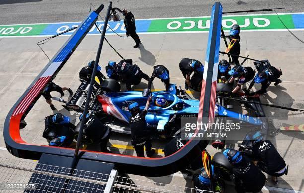 Alpine's mechanics work on the car of Alpine's Spanish driver Fernando Alonso in the pit lane during a practice session at the Autodromo...