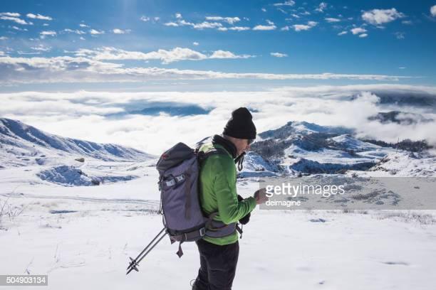 Alpinist Schecks Telefon auf schneebedeckte Berge