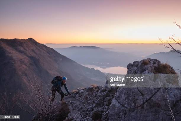 alpinist moving up on mountain, twilight - forza italia foto e immagini stock