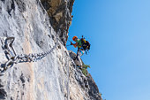 Alpinist on equipped rockface