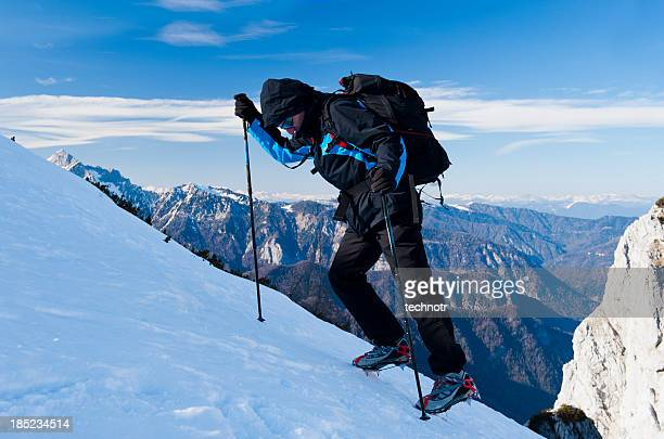 Alpinist on winter trip in the mountains using crampons