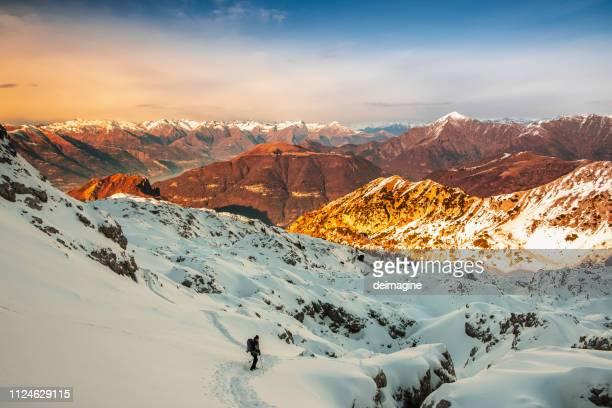 alpinista a piedi sulla montagna innevata - lombardia foto e immagini stock
