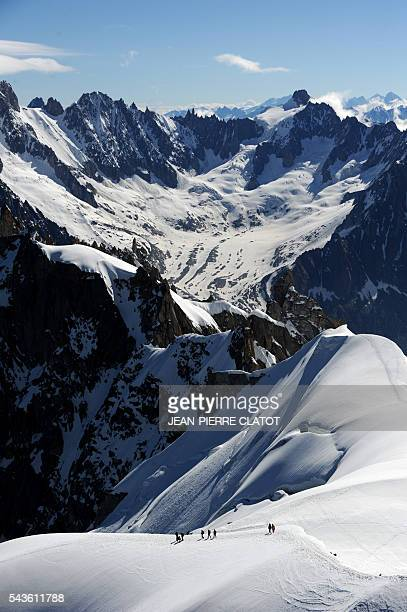 Alpinists walk on the MontBlanc Massif above the vallee blanche in the French Alps on June 29 2016 / AFP / JEANPIERRE CLATOT