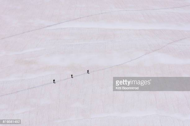 alpinists walking on glacier of col du midi, france - aiguille de midi stock photos and pictures