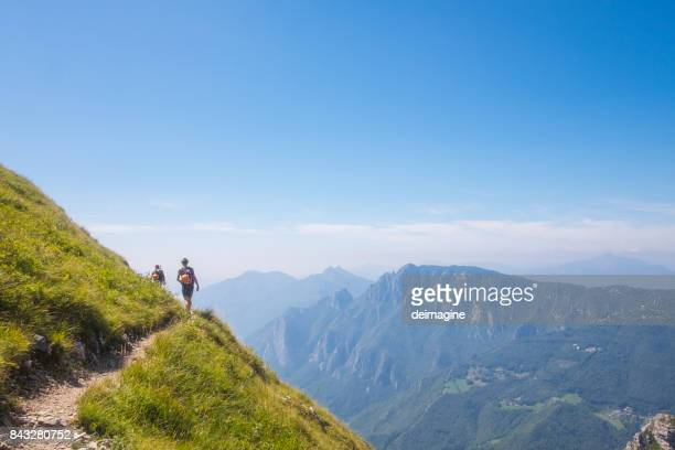 alpinists walking on high mountain path - swiss alps stock pictures, royalty-free photos & images