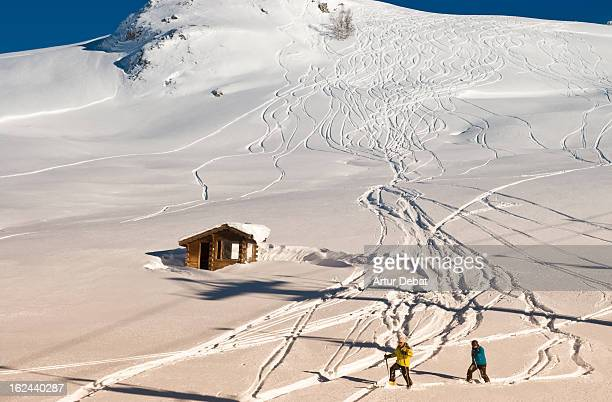 CONTENT] Alps Alpes France skiers cabin riders tracks snow snowy sunny day landscape mountain summit peak white blue sky wood couple europe leisure...
