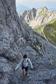 'Alps, Karwendel Mountains, woman hiking at Via ferrata'