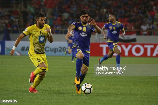 AlQuwa alJawiya's Iraqi striker Hammadi Ahmad vies for the ball against AlAhed SC's Lebanese defender Hussein Al Zain during their AFC Cup semifinal...