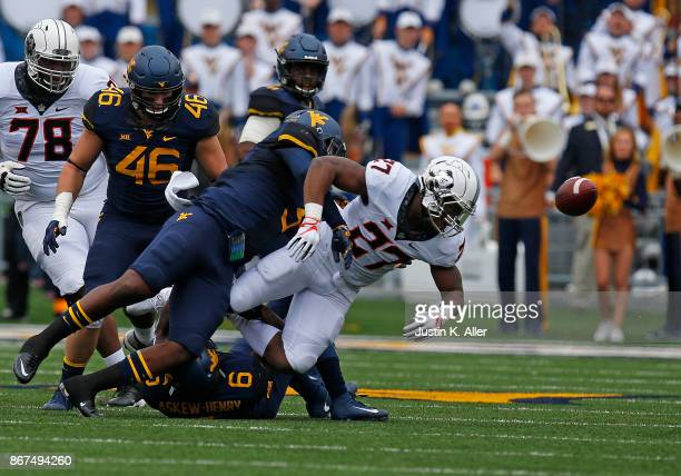 AlRasheed Benton of the West Virginia Mountaineers causes JD King of the Oklahoma State Cowboys to fumble at Mountaineer Field on October 28 2017 in...