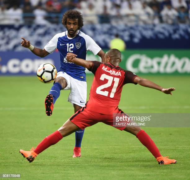 AlRayyan's Mohammed Juma views for the ball against alHilal's Yasir Shahrani during the AFC Champions League football match between Saudi alHilal and...