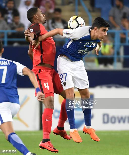AlRayyan's Musa Haroom views for the ball against alHilal's Achraf Bencharki during the AFC Champions League football match between Saudi alHilal and...