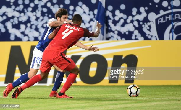 AlRayyan's Musa Haroon views for the ball against alHilal's Ezequiel Cerutti during the AFC Champions League football match between Saudi alHilal and...