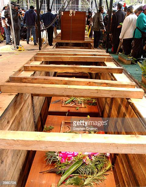 Already lowered caskets adorned with flowers are seen in the foreground as workers lower more caskets during the reinterment ceremony at the African...