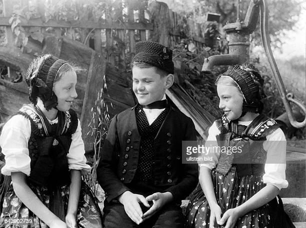 Alsace in 2 WW under german occupation Two girls and a boy from Alsace wearing typical costumes ca 1940 Photographer Erich Engel Published by 'Die...