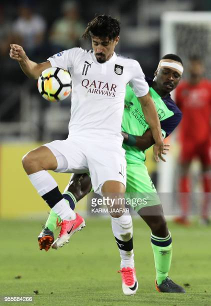 AlSadd's Baghdad Boudnejah controls the ball as AlAhli's defender Motaz Hawsawi defends during the AFC Champions League football match between...