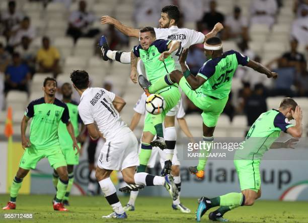 TOPSHOT AlSadd's Morteza Pouraliganji and Baghdad Bounedjah vie for the ball against AlAhli's Claudemir de Souza and Mortaz Hawsawi during the AFC...