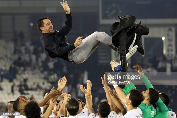 Al-Sadd's Spanish coach Xavi is thrown into the air by his players as they celebrate winning the final match of the Qatar Cup against Al-Duhail at...