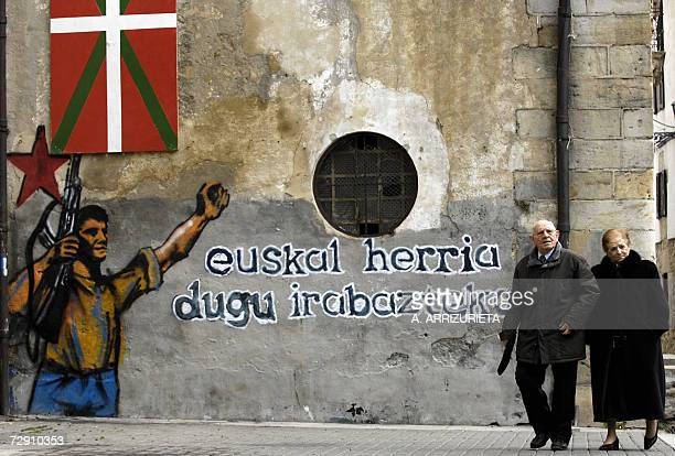 People walk past a graffitti reading we have got Basque country for to win 01 January 2007 in the northern Spanish Basque town of Alsasua two days...