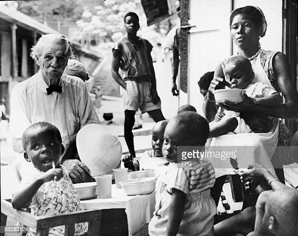 Alsatianborn German theologian musician physician and medical missionary Albert Schweitzer sits at a table with young children as they eat a meal at...